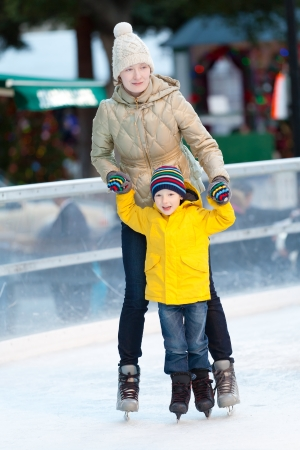 happy smiling mother and her cute cheerful son ice skating together at winter photo