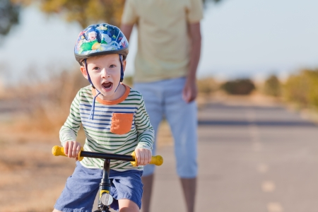 cheerful little boy in helmet at balance bike