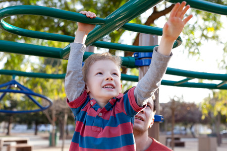 little positive boy at the monkey bars and his father watching and helping photo