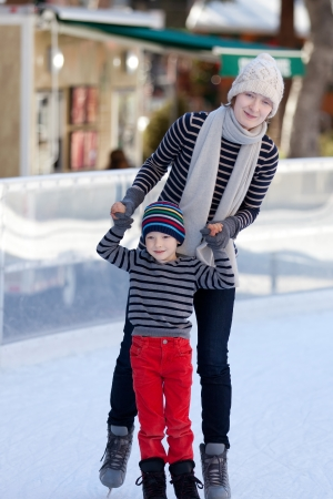 cheerful mother and her little son enjoying ice skating together at winter photo