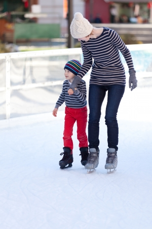 cheerful mother and her little son enjoying ice skating together at winter Reklamní fotografie