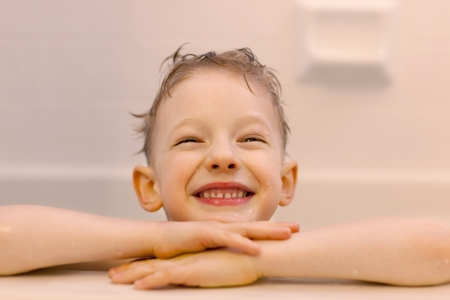 cheerful smiling little boy taking a bath at home photo