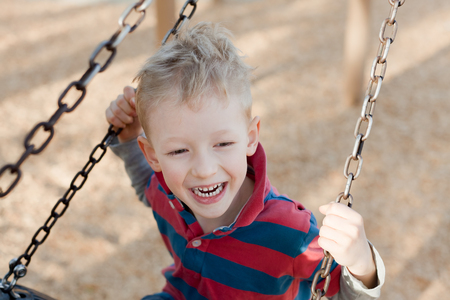 little laughing boy swinging at the playground photo