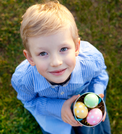 cute smiling little boy looking up and holding bucket with colorful eggs at easter time photo