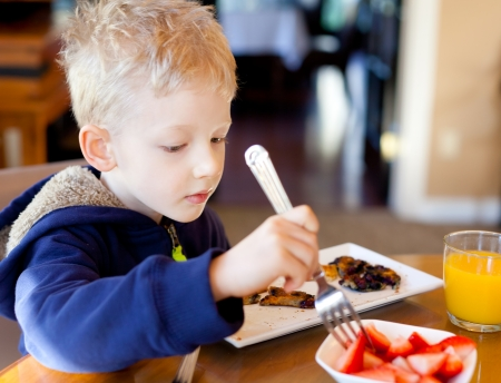 cute positive boy eating strawberries and pancakes at breakfast photo