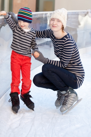 happy family of two enjoying ice skating at winter  photo