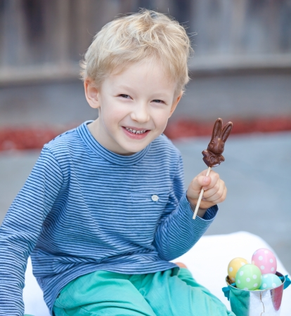 positive smiling boy holding chocolate rabbit at easter time photo