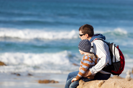 young father and his little son sitting together at the beach photo