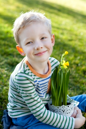 cute smiling little boy holding white pot with blooming daffodils at spring time photo