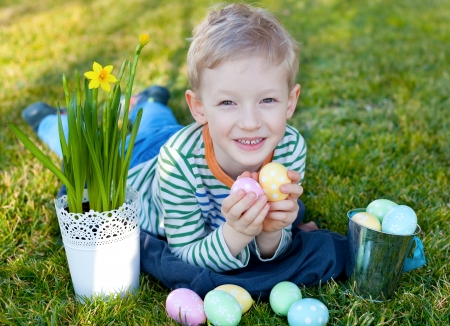 cute little boy with basket full of colorful easter eggs at spring time