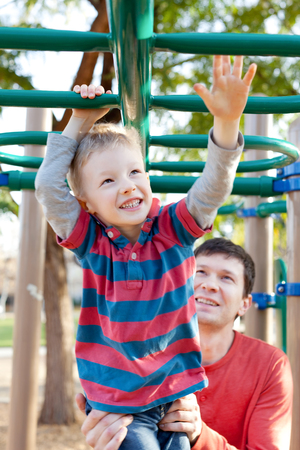 cheerful little boy playing at monkey bars and his father helping him at the playground photo