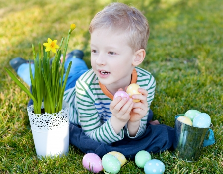 cheerful positive little boy holding colorful eggs at easter time photo