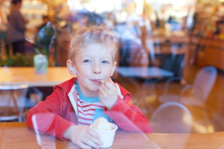 cute little boy enjoying ice cream in cafe, view from outside photo