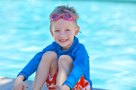 cute smiling boy in colorful swimwear and goggles sitting by the pool photo