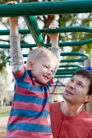cheerful smiling boy and his handsome young father having fun at the playground together photo