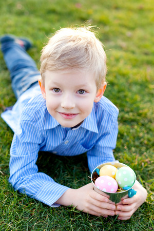 easter egg hunt: cute smiling boy with basket full of colorful easter eggs lying at green grass at spring time