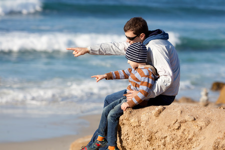family of father and son sitting together on the rock looking at the ocean and pointing at something photo