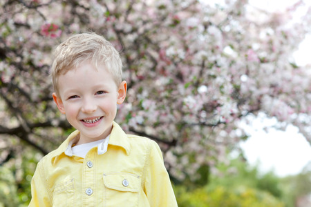 cheerful smiling little boy with beautiful blooming apple tree in the background at spring time photo
