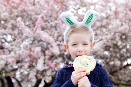 smiling little boy with bunny ears holding lollipop and beautiful blooming tree in the background at easter time   photo