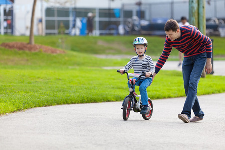 les geven: jonge vader onderwijs zijn glimlachende zoon hoe om een fiets te rijden Stockfoto