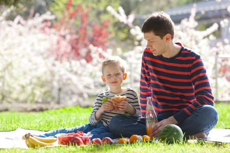family of two having a picnic at summer, eating sandwiches and drinking juice photo