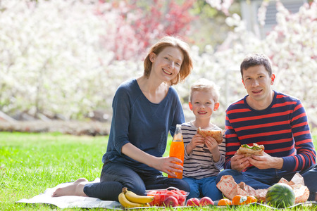 happy smiling family of three having a picnic outside together, eating sandwiches and fruits photo