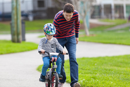 training wheels: young handsome father teaching his son to ride a bike