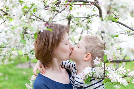 young mother kissing and hugging her son by the blooming tree photo