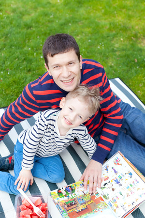 father and son having picnic together and reading a book outside photo