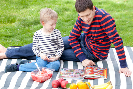 handsome young father and his son having fun time together at picnic outside photo