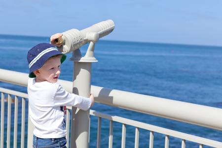 little positive boy using seaside binoculars and enjoying the view photo
