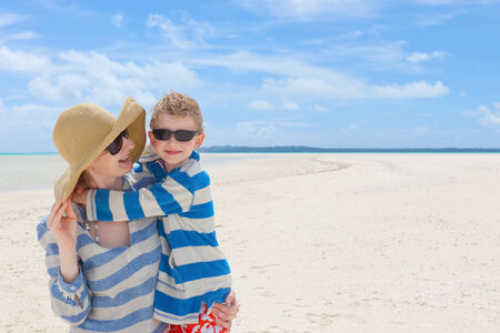 happy young beautiful mother and her smiling cheerful son hugging and spending fun time together at picture perfect beach, tropical vacation  photo