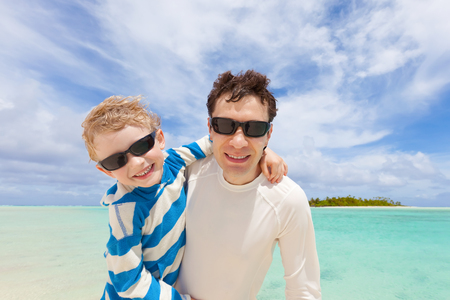 positive smiling boy and his young handsome father having fun at tropical beach, perfect vacation photo