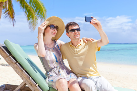 positive smiling couple taking picture at the perfect beach photo