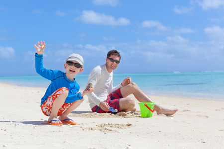 positive smiling family building sand castle and spending fun time at the beach, little boy waving photo