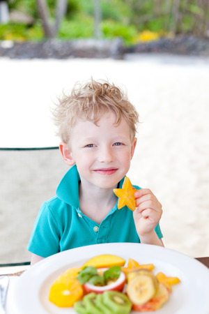 cute positive little boy eating exotic fruit during his tropical vacation at the beach photo