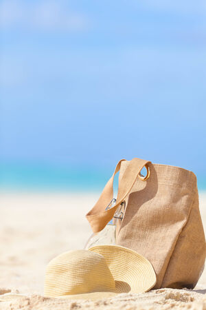 closeup of beach bag, sunhat and bottle of water at empty perfect beach, tropical vacation concept photo