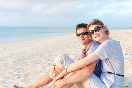 smiling loving couple spending time together at perfect empty beach during tropical vacation photo