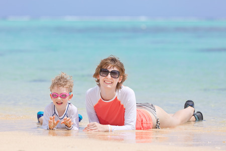 motu: happy family of two lying at perfect beach during tropical vacation