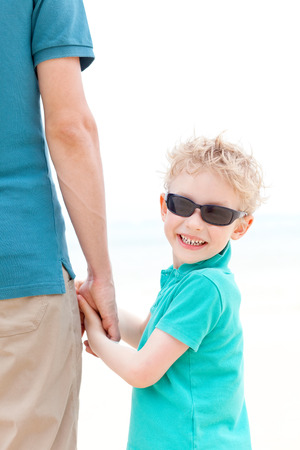 smiling positive boy holding his father hands at the beach photo