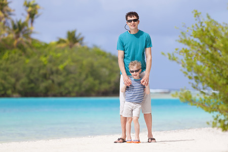 handsome father and his smiling son standing together at beautiful perfect beach, gorgeous lagoon view photo