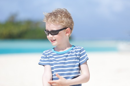motu: portrait of smiling little boy standing at picture perfect beach Stock Photo