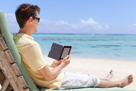 handsome man at the beach reading his electronic reader photo