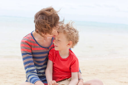 motu: family of mother and her little son sitting at the beach together, hugging and having fun during vacation
