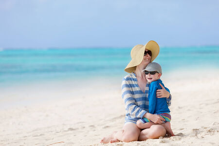 beautiful smiling mother and her cheerful little son sitting at the beach together and having fun during vacation photo