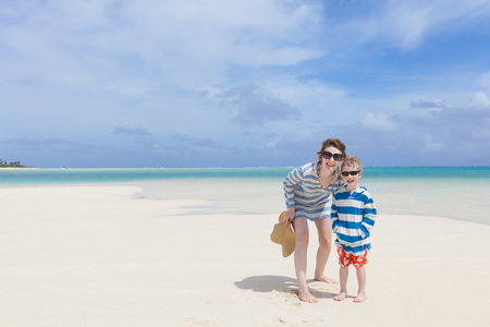 motu: cheerful smiling family of mother and her son standing at the perfect beach, tropical vacation together