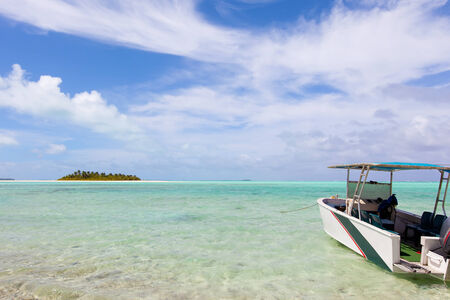 motu: picture perfect view at the island, breathtaking lagoon and anchored boat at cook islands, aitutaki