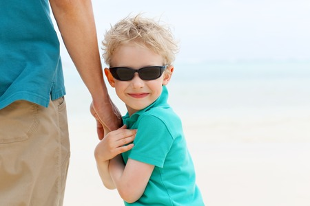 fun day: smiling cute boy holding his fathers hand, having fun day with father, family vacation
