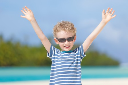 motu: cheerful little boy standing with hands up at the tropical gorgeous beach Stock Photo