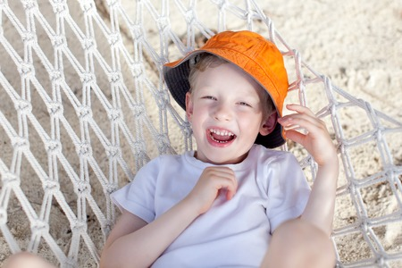 motu: laughing little boy having fun lying in the hammock at the beach